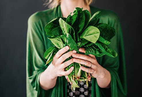woman in green holding spinach