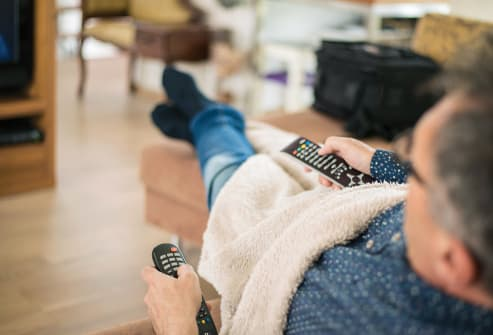 mature man on sofa using tv remote