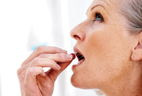 mature woman taking pill close up