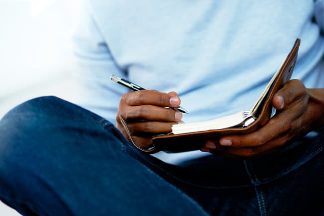 photo of man writing in journal