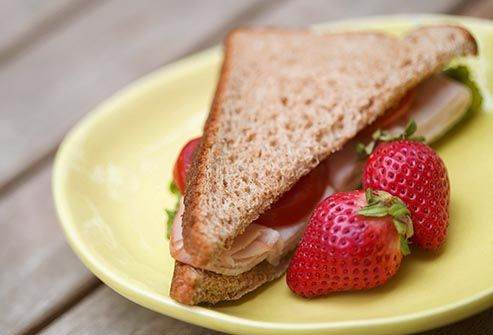 half turkey sandwich and strawberries