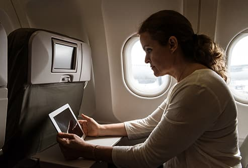 woman using tablet on plane