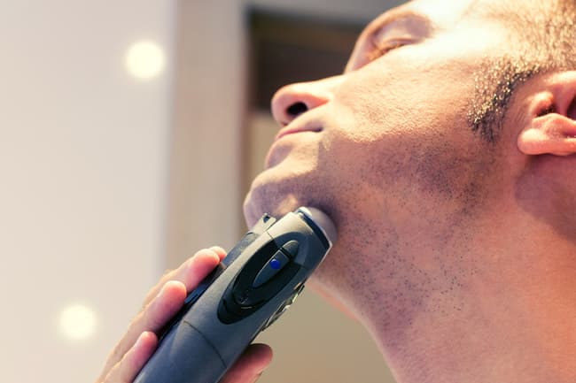 photo of man shaving with electric razor