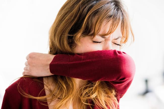 photo of woman sneezing into sleeve