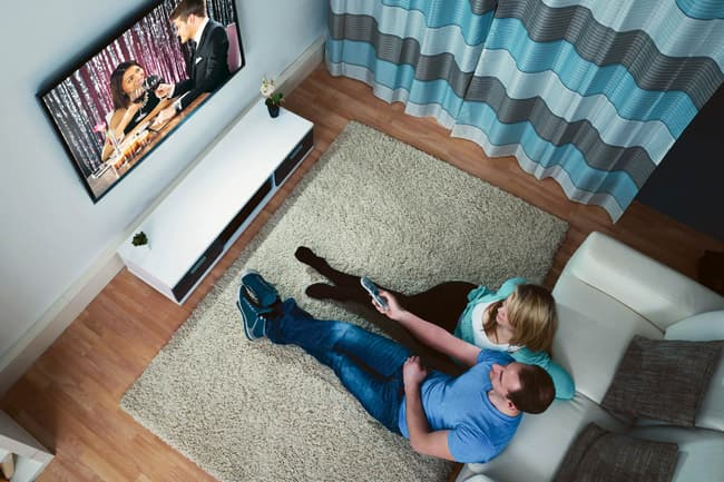 couple on floor watching tv