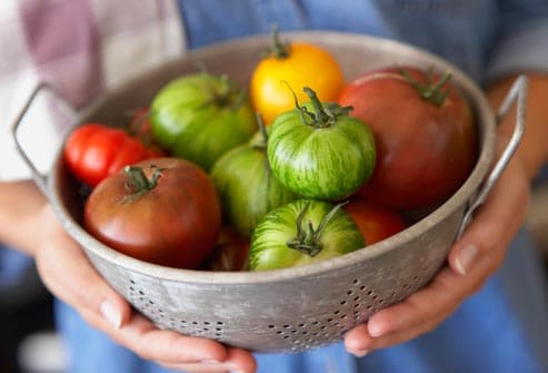woman holding heirloom tomatoes