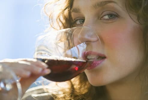Young Woman Drinking a Glass of Red Wine