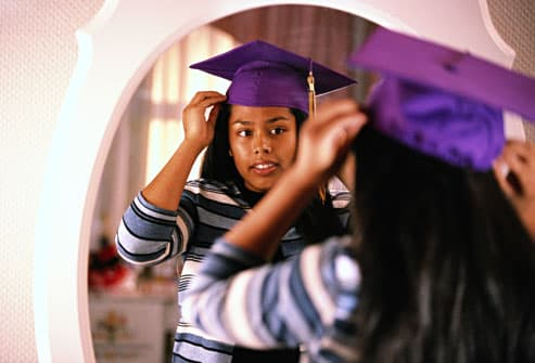 teen girl trying on graduation cap