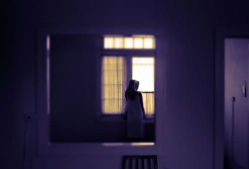 Woman in a dark, gloomy room looking out a window