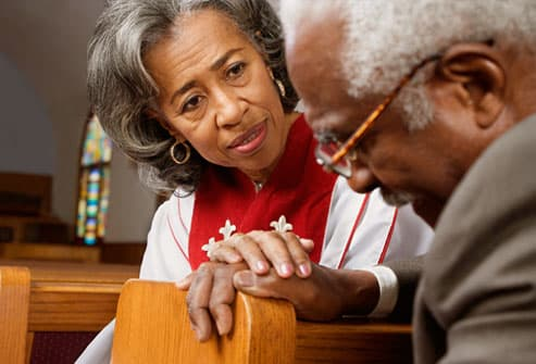 Female reverend counseling an elderly man in pew