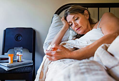 Woman in bed looking at medication