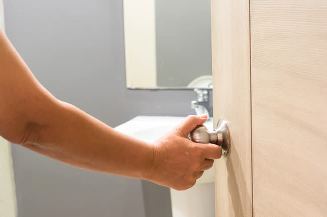 photo of hand opening bathroom door