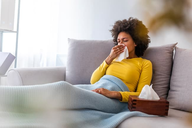 photo of woman sick on couch