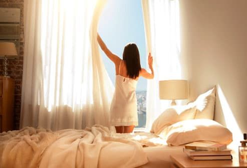 Woman opening her curtains to the morning light