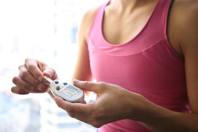 photo of woman using glucometer
