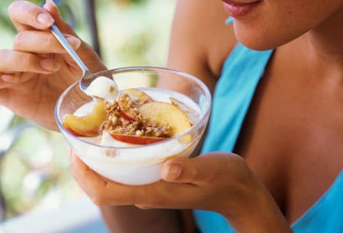 Woman Eating Bowl of Yogurt and Fruit