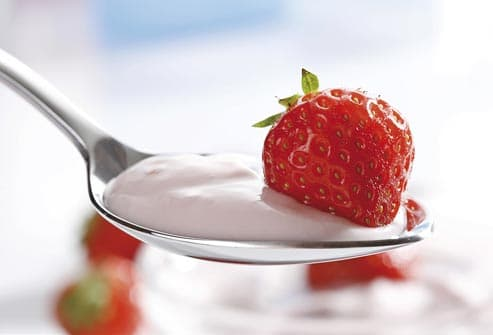 strawberry in spoonful of yogurt
