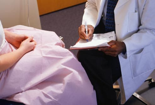 woman in exam room talking to doctor