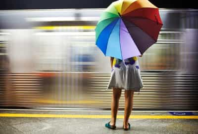 woman with umbrella waiting for train