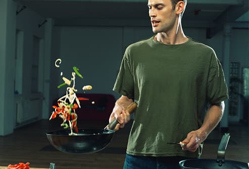 Man flipping vegetables in wok