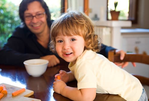 Father and daughter in dining room eating carrots
