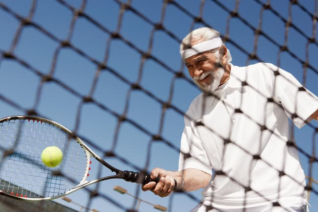 mature man playing tennis