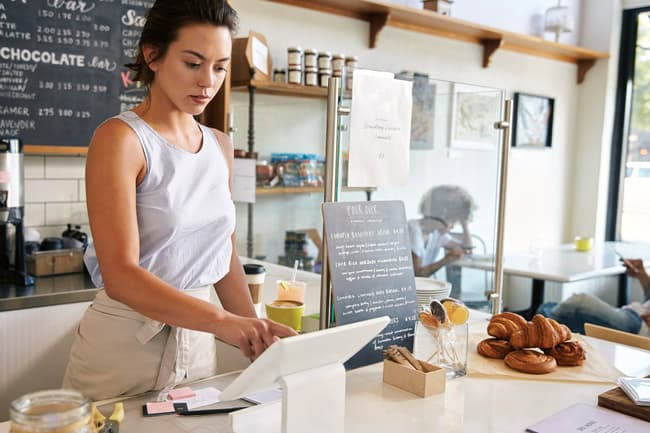 woman working till at coffee shop