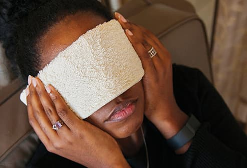 woman applying compress to eyes