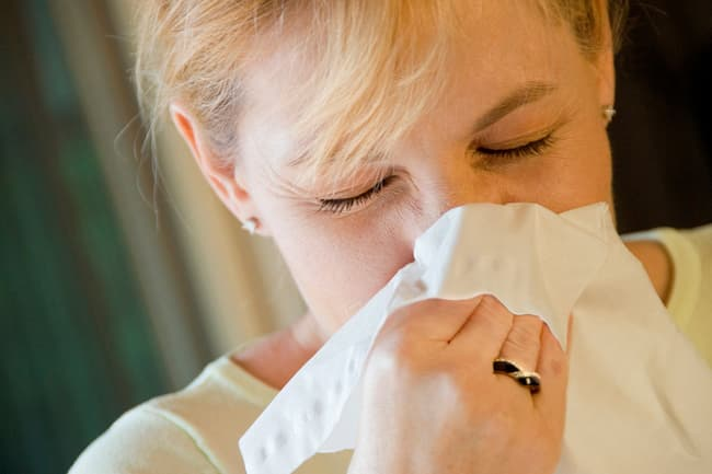 photo of woman blowing her nose