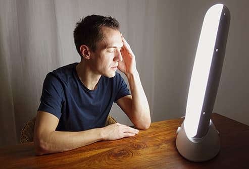 man sitting by light box