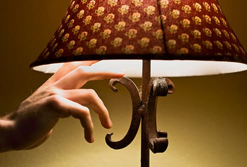 hand turning off lamp