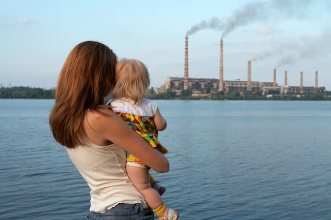 mother and daughter watching factory smoke