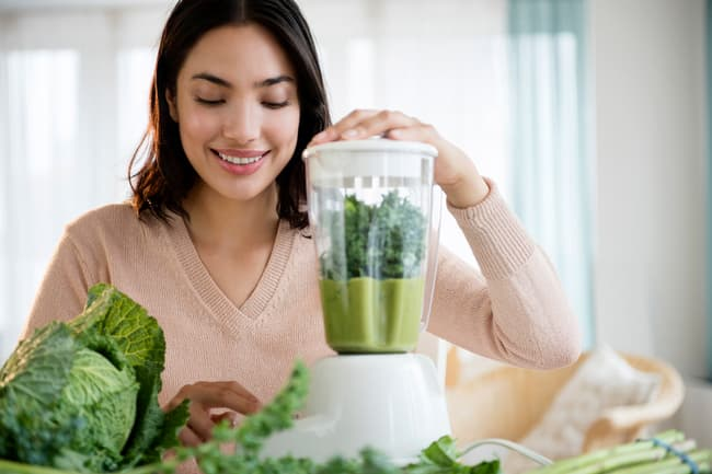 photo of woman making smoothie