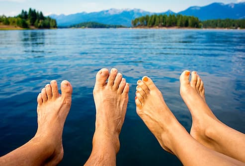 bare feet dangling over mountain lake