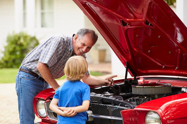 photo of man and grandson with car