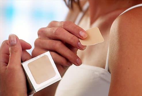 Woman applying nicotine patch to shoulder