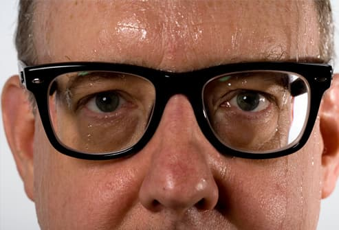 Man wearing glasses, sweating, close-up