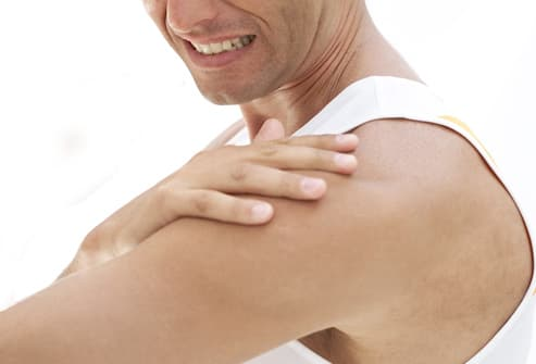 young man touching his shoulder in pain