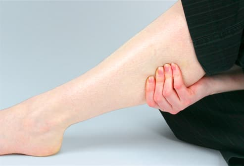 Woman holding sore muscle on leg