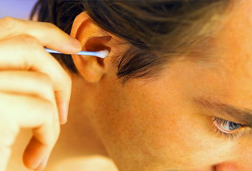 Man cleaning his ear with a cotton swab