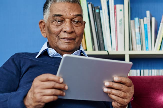 photo of mature man using tablet