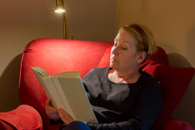 photo of mature woman using reading light