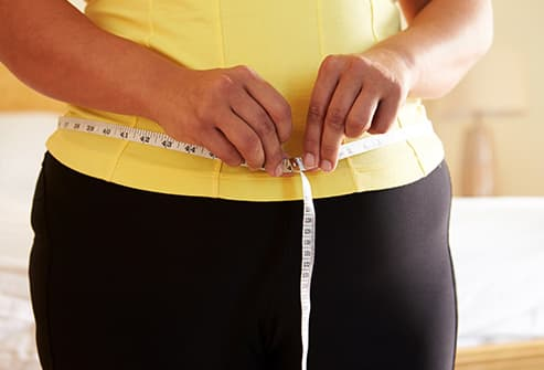 woman measuring waist close up