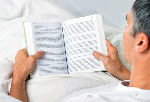 man lying on bed reading
