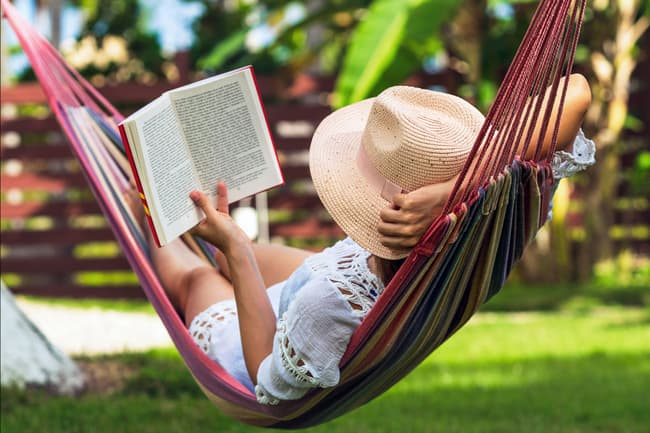 photo of woman in hammock reading book