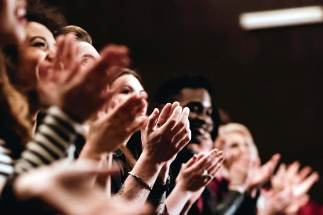 photo of hands clapping at performance