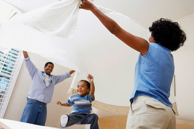 family changing bed sheets