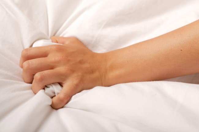 hand grasping bed
