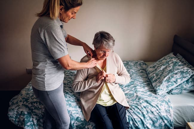 mature woman getting dressed with help