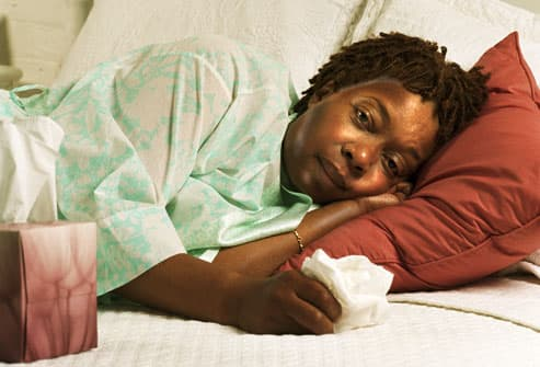 Feverish woman sweating while in bed